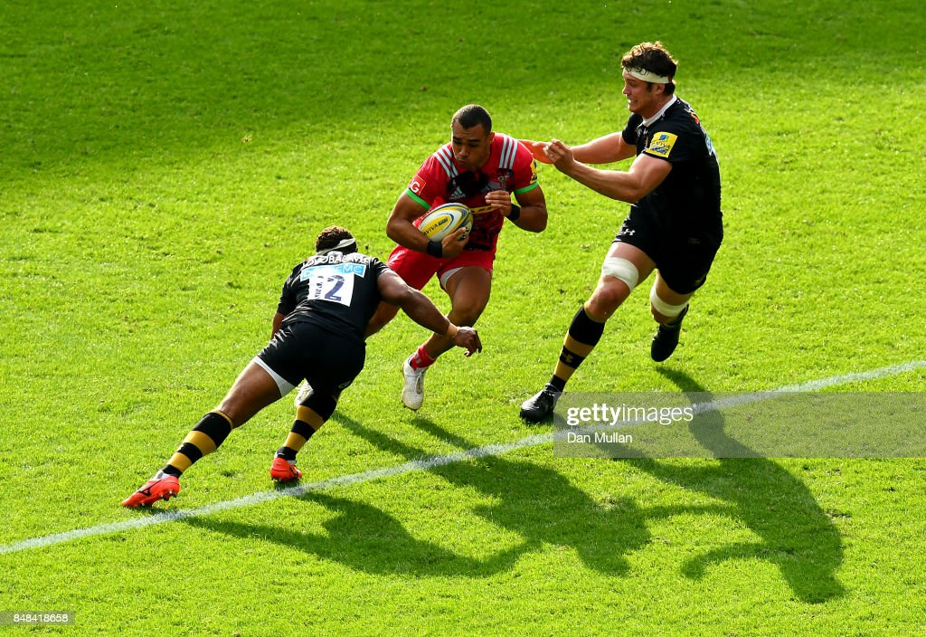 Joe Marchant of Harlequins is tackled by Gabiriele Lovobalavu and Will Rowlands of Wasps during the Aviva Premiership match between Wasps and Harlequins at The Ricoh Arena on September 17, 2017 in Coventry, England.