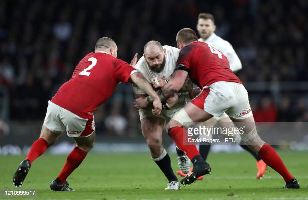 Joe Marler of England is tackled by Ken Owens and Jake Ball of Wales during the 2020 Guinness Six Nations match between England and Wales at...