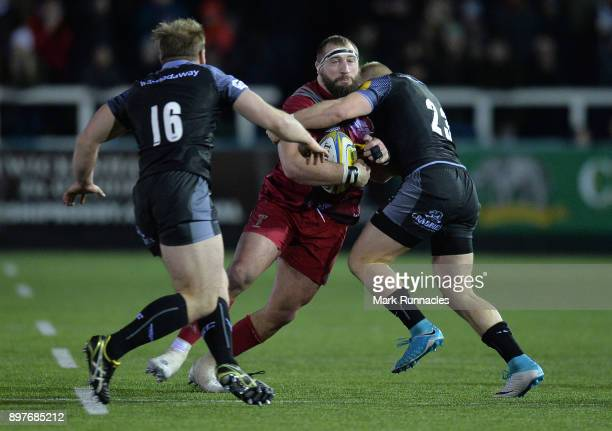 Joe Marler of Harlequins is tackled by Alex Tait and Ben Sowrey of Newcastle Falcons during the Aviva Premiership match between Newcastle Falcons and...