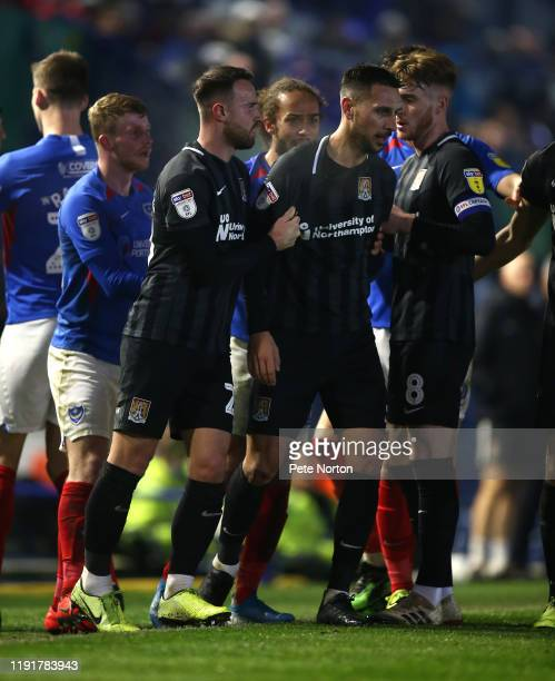 Joe Martin of Northampton Town is restrained by teammates after a clash with James Bolton of Portsmouth during the Leasingcom Trophy match between...