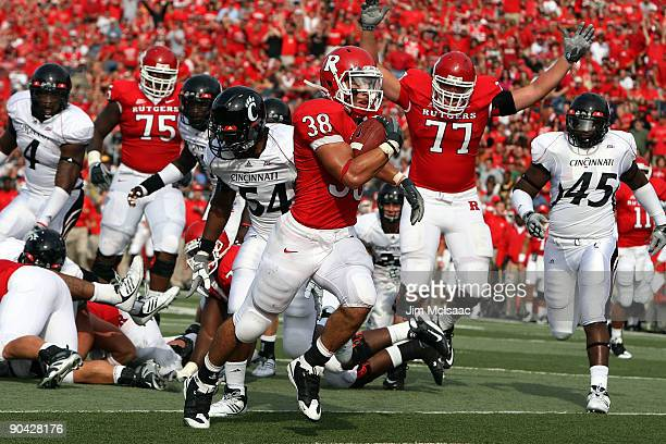 Joe Martinek of the Rutgers Scarlet Knights runs in a touchdown against the Cincinnati Bearcats at Rutgers Stadium on September 7, 2009 in...