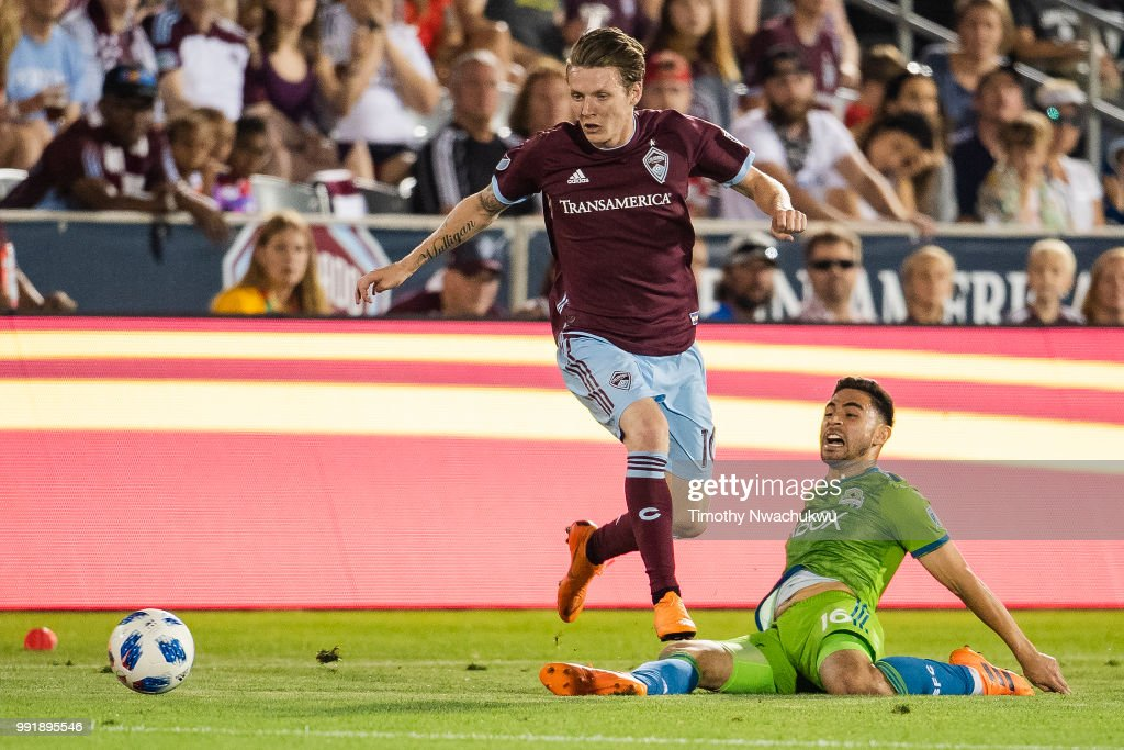 Joe Mason #10 of Colorado Rapids dribbles over Alex Roldan #16 of Seattle Sounders at Dick's Sporting Goods Park on July 4, 2018 in Commerce City, Colorado.