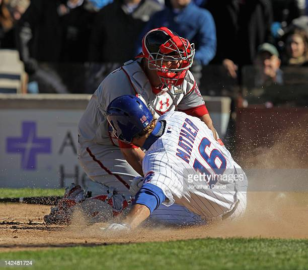 Joe Mather of the Chicago Cubs is tagged out at the plate by Wilson Ramos of the Washington Nationals during the opening day game at Wrigley Field on...