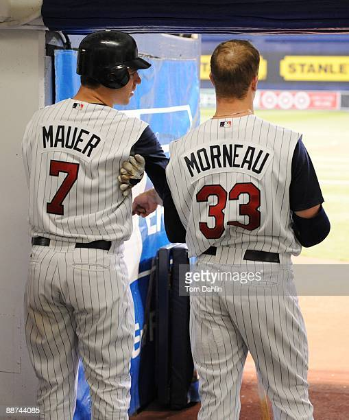 Joe Mauer and Justin Morneau of the Minnesota Twins await their turn at bat during an MLB game against the Pittsburgh Pirates at the Hubert H....