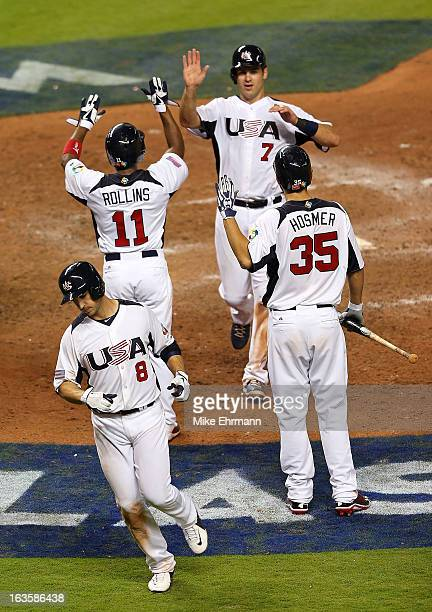 Joe Mauer Jimmy Rollins and Ryan Braun of the United States are congratulated by Eric Hosmer after scoring on a bases loaded double by David Wright...