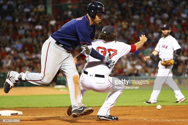 Joe Mauer of the Minnesota Twins collides with Heath Hembree of the Boston Red Sox as he drops the ball at first base in the eighth inning of a game...