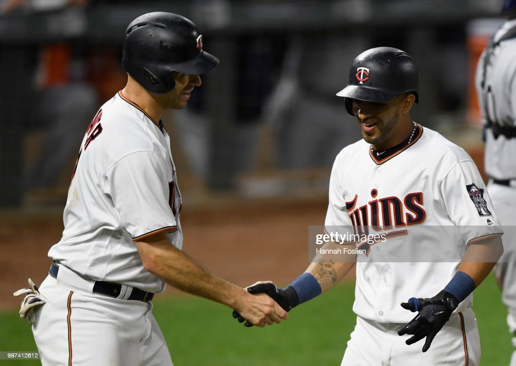 Joe Mauer #7 of the Minnesota Twins congratulates teammate Eddie Rosario #20 on a two-run home run against the Tampa Bay Rays during the seventh inning of the game on July 12, 2018 at Target Field in Minneapolis, Minnesota. The Twins defeated the Rays 5-1.