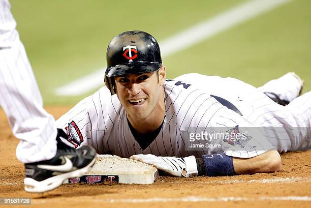 Joe Mauer of the Minnesota Twins dives back toward first after a single during the American League Tiebreaker game against the Detroit Tigers on...