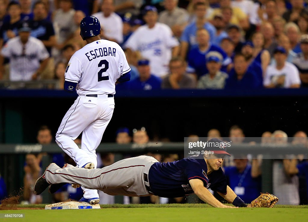 Joe Mauer #7 of the Minnesota Twins dives off the bag for a poorly thrown ball as Alcides Escobar #2 of the Kansas City Royals is safe at first during the 8th inning of the game at Kauffman Stadium on August 27, 2014 in Kansas City, Missouri.