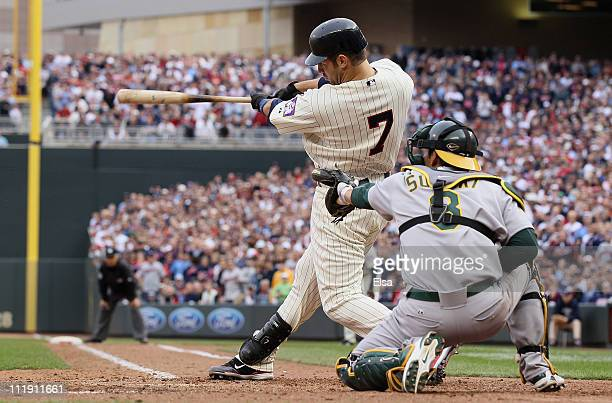 Joe Mauer of the Minnesota Twins drives in the winning run as Kurt Suzuki of the Oakland Athletics catches during Opening Day on April 8 2011 at...
