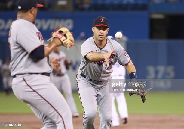 Joe Mauer of the Minnesota Twins flips the ball to Adalberto Mejia covering first base to get the baserunner for the final out of the first inning...