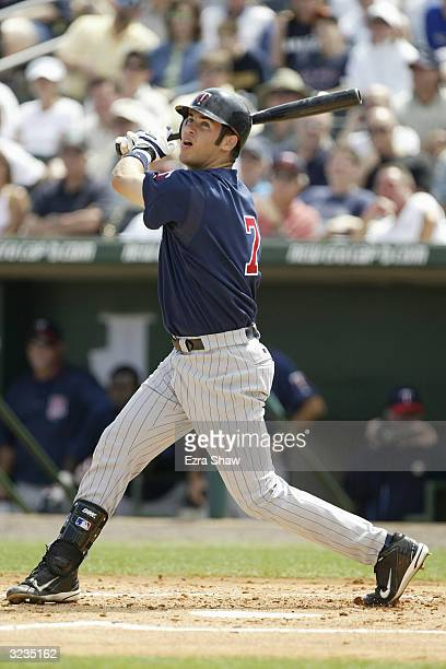 Joe Mauer of the Minnesota Twins follows through on his swing against the Florida Marlins during their game on March 11 2004 at Roger Dean Stadium in...