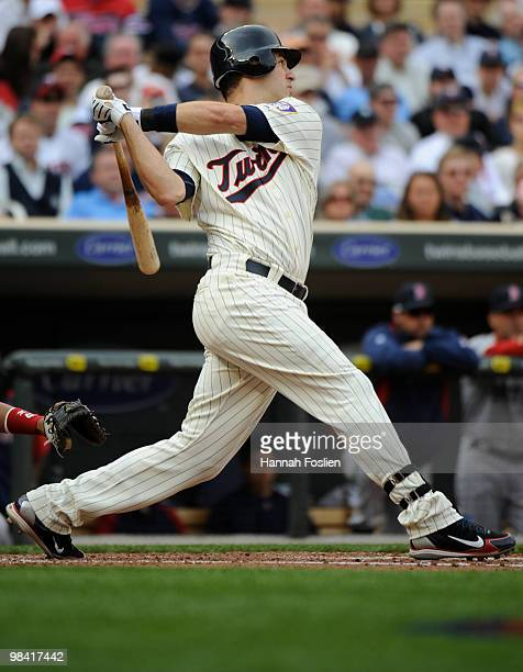 Joe Mauer of the Minnesota Twins hits an RBI double in the second inning against the Boston Red Sox during the Twins home opener at Target Field on...