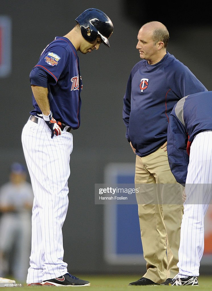 Joe Mauer #7 of the Minnesota Twins is checked by trainer Tony Leo after hitting a double against the Kansas City Royals during the sixth inning of the game on July 1, 2014 at Target Field in Minneapolis, Minnesota.