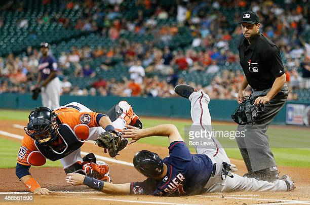 Joe Mauer of the Minnesota Twins is tagged out by Hank Conger of the Houston Astros in the first inning at Minute Maid Park on September 4 2015 in...