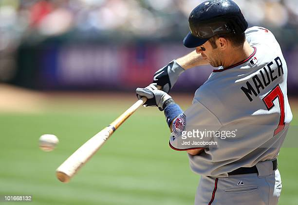 Joe Mauer of the Minnesota Twins makes contact with the ball against the Oakland Athletics during an MLB game at the OaklandAlameda County Coliseum...