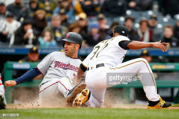 Joe Mauer of the Minnesota Twins slides in safe on a wild pitch against Edgar Santana of the Pittsburgh Pirates in the sixth inning during...