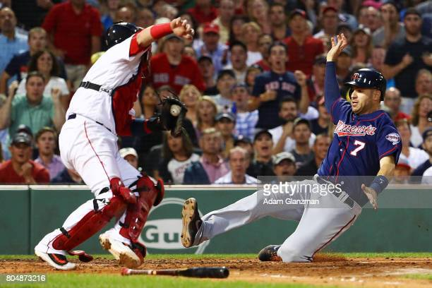 Joe Mauer of the Minnesota Twins slides past the tag of Christian Vazquez of the Boston Red Sox in the fourth inning of a game at Fenway Park on June...