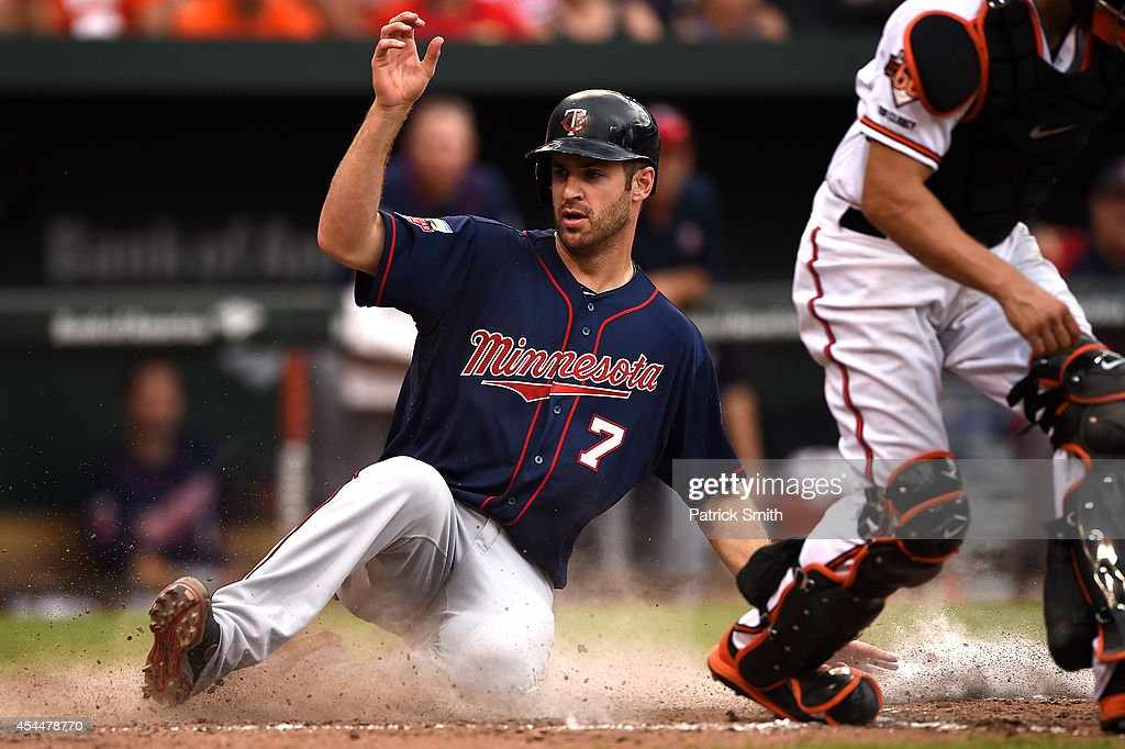 Joe Mauer #7 of the Minnesota Twins slides safe into home plate against the Baltimore Orioles in the eighth inning at Oriole Park at Camden Yards on September 1, 2014 in Baltimore, Maryland. The Minnesota Twins won, 6-4.