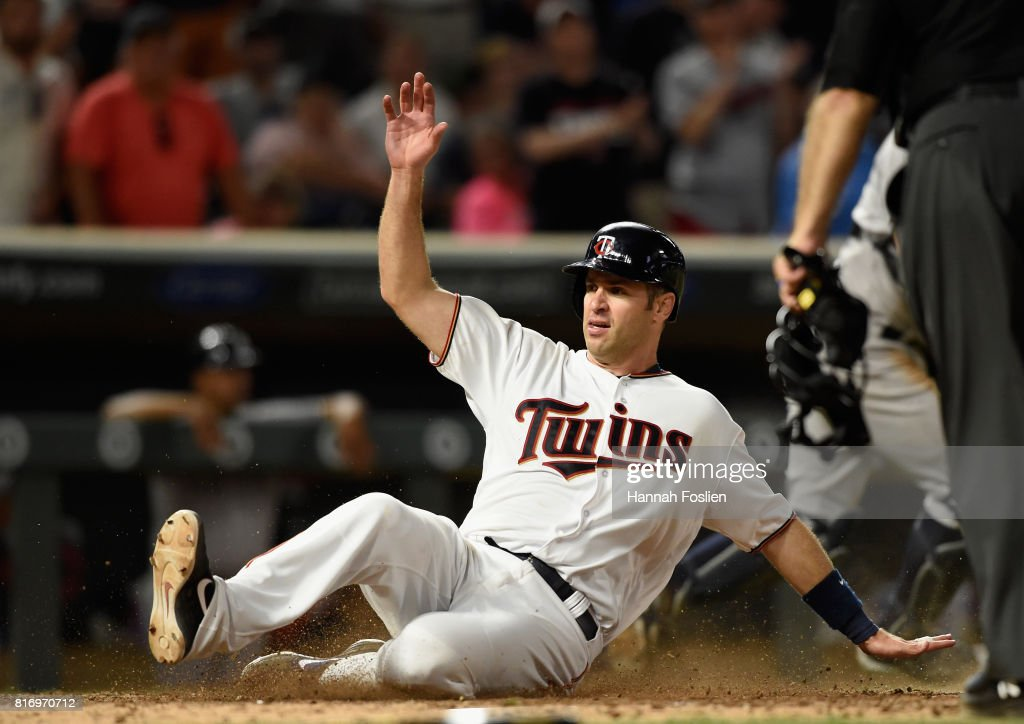 Joe Mauer #7 of the Minnesota Twins slides safely into home plate to score a run against the New York Yankees during the eighth inning of the game on July 17, 2017 at Target Field in Minneapolis, Minnesota. The Twins defeated the Yankees 4-2.