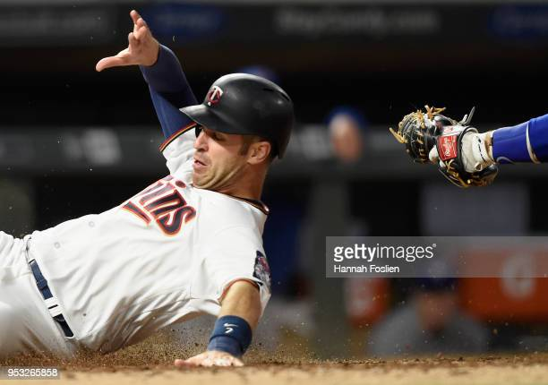 Joe Mauer of the Minnesota Twins slides safely past Russell Martin of the Toronto Blue Jays to score a run during the seventh inning of the game on...