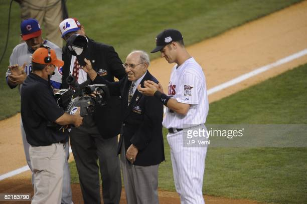 Joe Mauer of the Minnesota Twins stands next to Hall of Famer Yogi Berra before the 79th MLB AllStar Game at the Yankee Stadium in the Bronx New York...