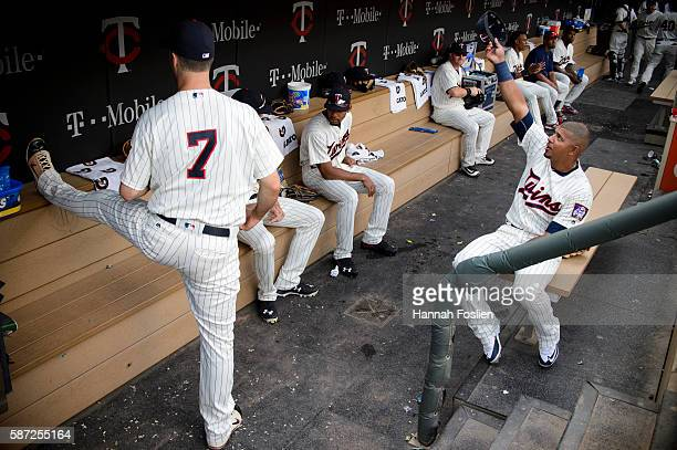 Joe Mauer of the Minnesota Twins stretches as teammate Eduardo Escobar waves his hat in the dugout as they wait for the start of the game against the...