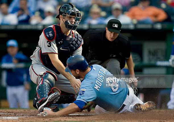 Joe Mauer of the Minnesota Twins tags out Mike Moustakas of the Kansas City Royals as he tries to score in the fourth inning at Kauffman Stadium on...