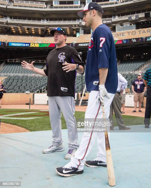 Joe Mauer of the Minnesota Twins talks with Mike Redmond of the Colorado Rockies against the Colorado Rockies on May 16 2017 at Target Field in...