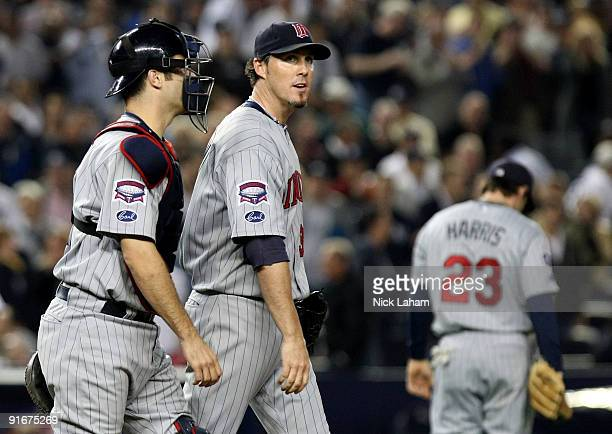 Joe Mauer talks with Joe Nathan of the Minnesota Twins after an erron in the tenth inning against the New York Yankees in Game Two of the ALDS during...