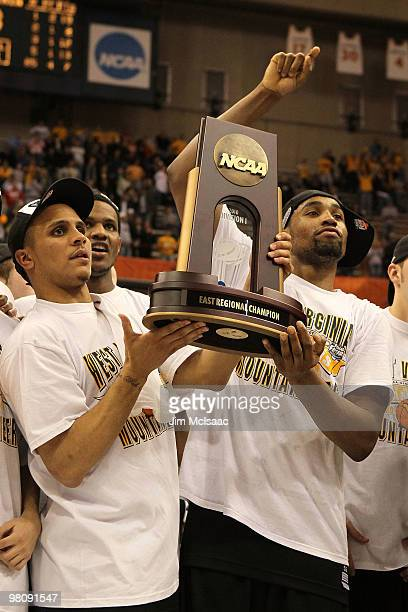 Joe Mazzulla and Da'Sean Butler of the West Virginia Mountaineers celebrate with the East Regional trophy after West Virginia won 73-66 against the...