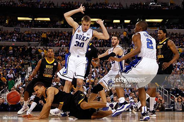 Joe Mazzulla of the West Virginia Mountaineers falls down as he goes after the ball next to Jon Scheyer of the Duke Blue Devils during the National...
