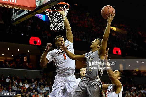 Joe McDonald of the George Washington Colonials drives to the basket against Justin Anderson of the Virginia Cavaliers in the first half during a...