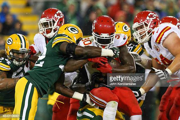 Joe McKnight of the Kansas City Chiefs is grabbed by Chris Banjo of the Green Bay Packers in the third quarter during the preseason game on August 28...
