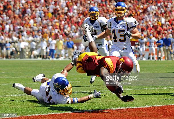 Joe McKnight of the USC Trojans dives into the end zone to score a touchdown against Tiuke Tuipulotu of the San Jose State Spartans during the second...