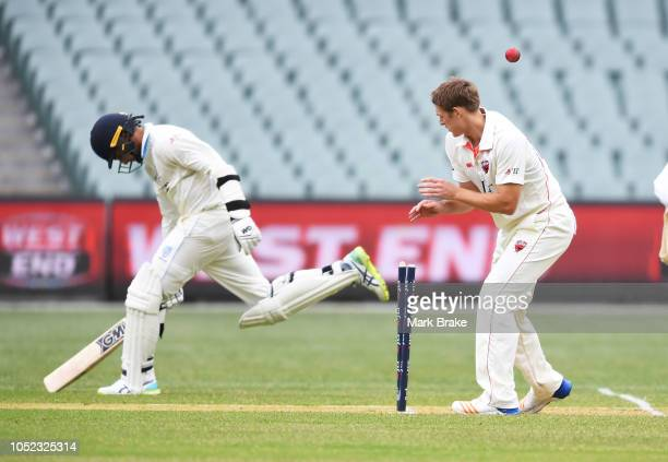 Joe Mennie of the Redbacks watches the ball hit the stumps as Jason Sangha of the Blues makes his crease during the Sheffield Shield match between...