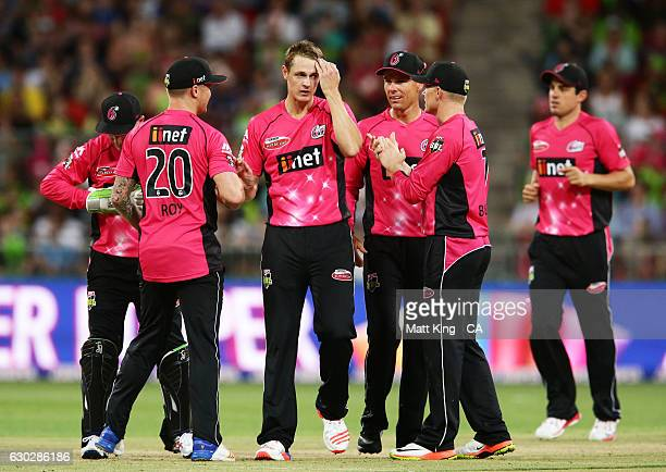 Joe Mennie of the Sixers celebrates with team mates after taking the wicket of Jake Doran of the Thunder during the Big Bash League match between the...