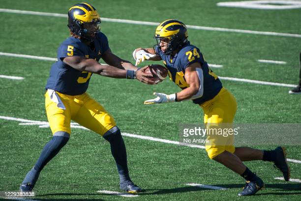 Joe Milton of the Michigan Wolverines hands the ball off to Zach Charbonnet of the Michigan Wolverines during the third quarter against the Michigan...