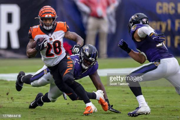 Joe Mixon of the Cincinnati Bengals carries the ball as Jaylon Ferguson and L.J. Fort of the Baltimore Ravens defend during the second half at M&T...