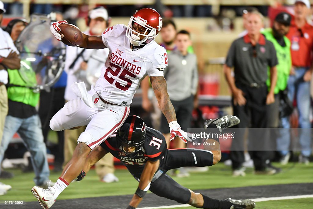 Joe Mixon #25 of the Oklahoma Sooners breaks the tackle of Justis Nelson #31 of the Texas Tech Red Raiders during the game on October 22, 2016 at AT&T Jones Stadium in Lubbock, Texas. Oklahoma won the game 66-59.
