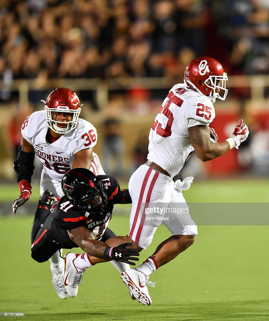 Joe Mixon #25 of the Oklahoma Sooners breaks the tackle of Malik Jenkins #41 of the Texas Tech Red Raiders during the game on October 22, 2016 at AT&T Jones Stadium in Lubbock, Texas. Oklahoma won the game 66-59.