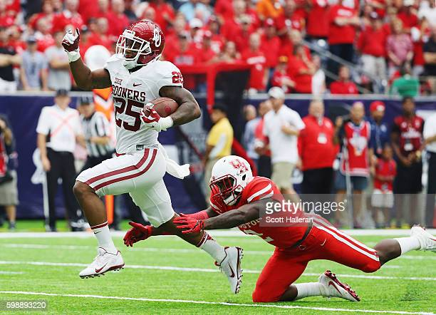 Joe Mixon of the Oklahoma Sooners races for a 32-yard touchdown past Khalil Williams of the Houston Cougars in the first half of their game during...