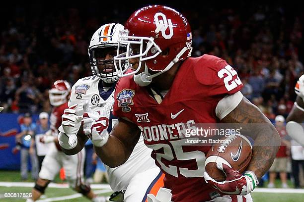 Joe Mixon of the Oklahoma Sooners runs with the ball against the Auburn Tigers during the Allstate Sugar Bowl at the MercedesBenz Superdome on...