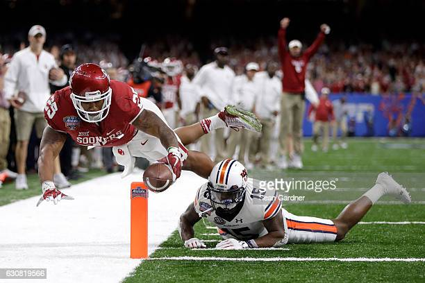 Joe Mixon of the Oklahoma Sooners scores a touchdown over Joshua Holsey of the Auburn Tigers during the Allstate Sugar Bowl at the Mercedes-Benz...