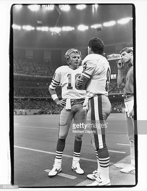 Joe Montana and Steve Young of the San Francisco 49ers discuss strategy during the game against the New Orleans Saints at the Louisiana Superdome on...