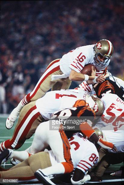 Joe Montana of the San Francisco 49ers dives over a pile of players to gain yardage against the Cincinnati Bengals during Superbowl XVI at the...