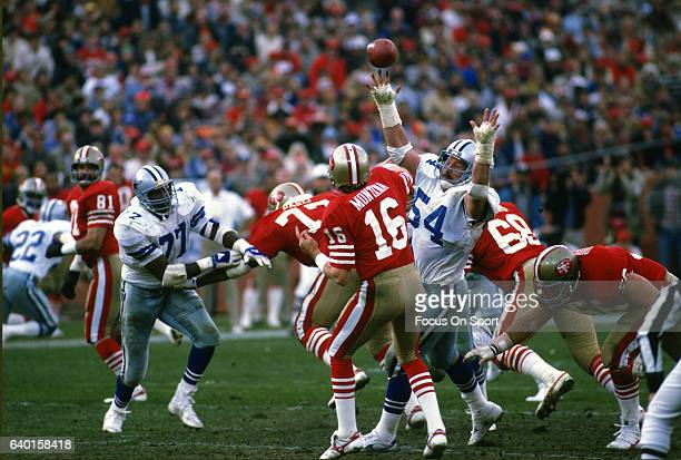 Joe Montana of the San Francisco 49ers gets his pass off under pressure from Randy White of the Dallas Cowboys during an NFL football game December...