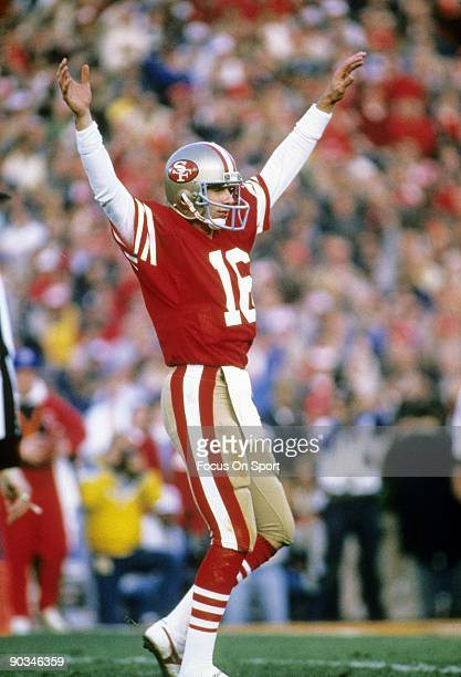 Joe Montana of the San Francisco 49ers throws his hand in the air after throwing a touchdown pass against the Miami Dolphins during Super Bowl XIX on...