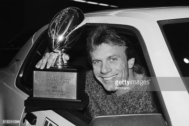 Joe Montana, quarterback of the world champion San Francisco 49ers, flashes Sport Magazine's MVP trophy given him for his super Super Bowl...