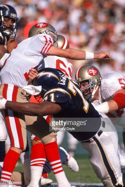 QB Joe Montana takes a hit after releasing the ball by a SD Charger defender San Francisco 49ers 48 vs San Diego Chargers 10 at Jack Murphy Stadium...